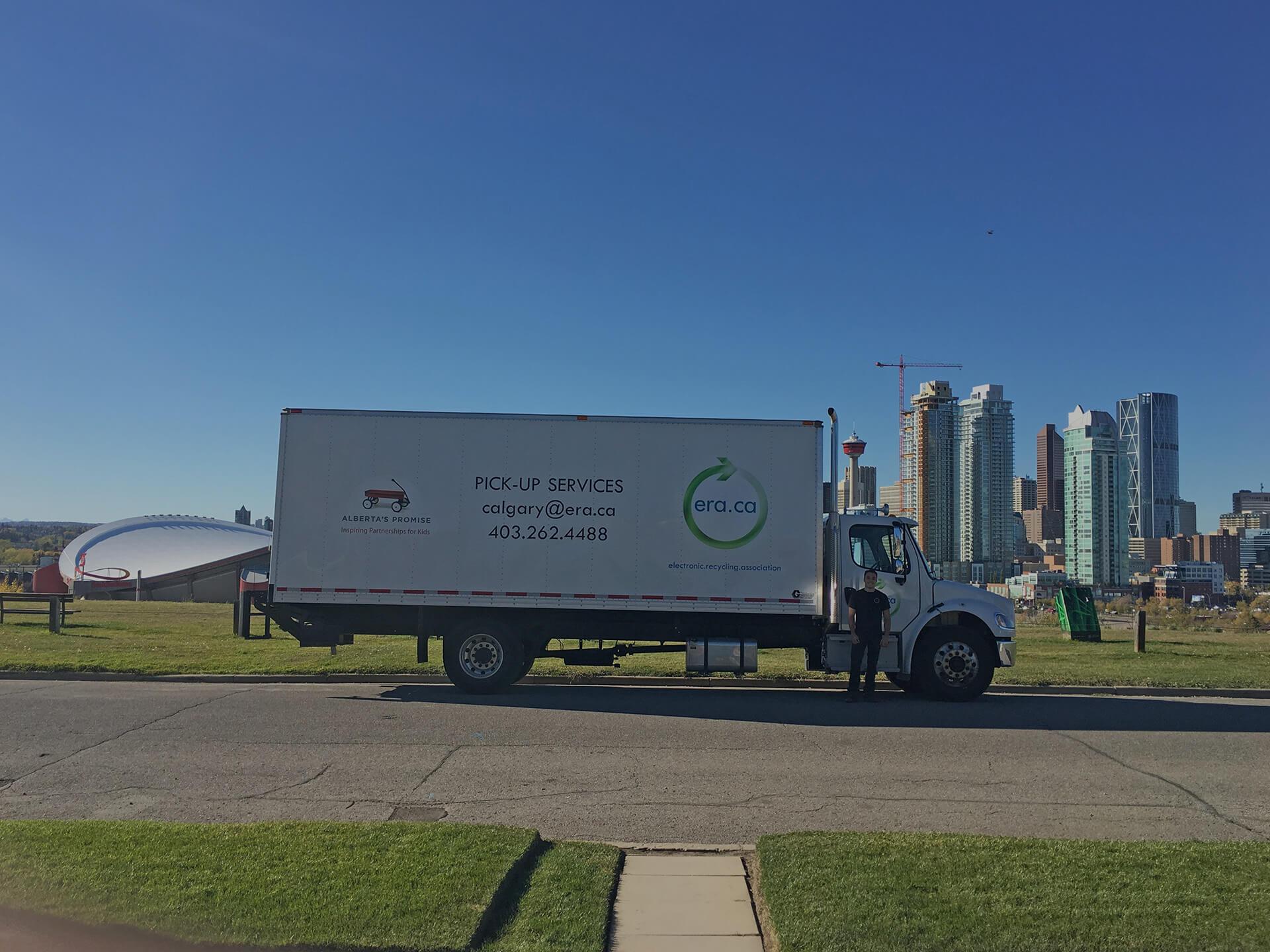 Camion de ramassage de l\'Association de Recyclage Électronique sur un terrain avec le centre-ville de Calgary en arrière-plan