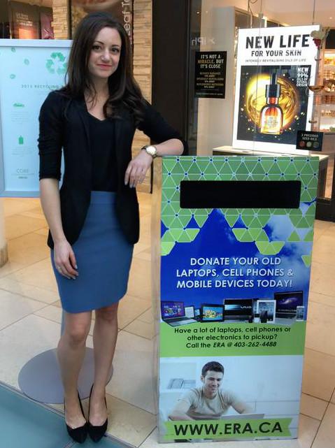 Femme poantr à côté d\'un  grand conteneur de collecte de l\'Association de Recyclage Électronique