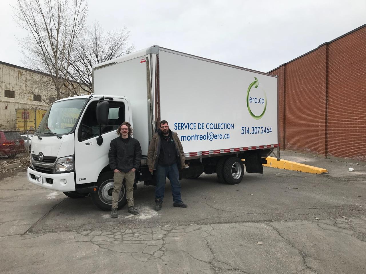 Deux agents de l\'Association de Recyclage Électronique posant à côté d\'un camion de ramassage dans un parking